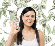 Woman shows ok sign. Dollar notes are falling down over isolated background. Royalty Free Stock Photos