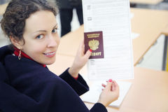 Woman shows passport and voting paper Stock Photography