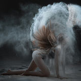 Woman shows a performance with flour. Her hair scatter the flour around the room stock image