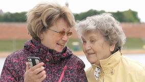 Woman shows photo to old woman using mobile phone. Two women stand on the background beautiful landscape outdoors. One woman dressed in sport jacket shows photos stock footage