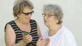 Woman shows photo to old woman using a smartphone stock footage