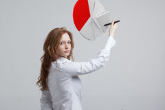 Woman shows a pie chart, circle diagram. Business analytics concept. Young Businesswoman shows a pie chart (circle diagram) on grey background. Business Stock Photo