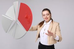 Woman shows a pie chart, circle diagram. Business analytics concept. Young Businesswoman shows a pie chart (circle diagram) on grey background. Business Royalty Free Stock Photos