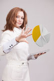 Woman shows a pie chart, circle diagram. Business analytics concept. Young Businesswoman shows a pie chart circle diagram on grey background. Business analytics Royalty Free Stock Image