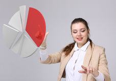 Woman shows a pie chart, circle diagram. Business analytics concept. Young Businesswoman shows a pie chart circle diagram on grey background. Business analytics Stock Image