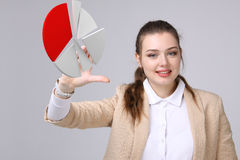 Woman shows a pie chart, circle diagram. Business analytics concept. Young Businesswoman shows a pie chart circle diagram on grey background. Business analytics Stock Photos
