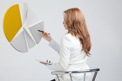 Woman shows a pie chart, circle diagram. Business analytics concept. Young Businesswoman shows a pie chart (circle diagram) on grey background. Business Royalty Free Stock Images