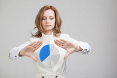 Woman shows a pie chart, circle diagram. Business analytics concept. Young Businesswoman shows a pie chart (circle diagram) on grey background. Business Stock Photography