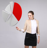 Woman shows a pie chart, circle diagram. Business analytics concept. Young Businesswoman shows a pie chart (circle diagram) on grey background. Business Royalty Free Stock Photo