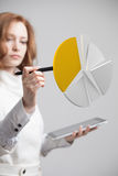 Woman shows a pie chart, circle diagram. Business analytics concept. Young Businesswoman shows a pie chart (circle diagram) on grey background. Business Royalty Free Stock Photography