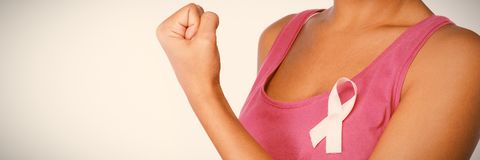 Woman shows pink ribbon for breast cancer awareness. On white background stock images