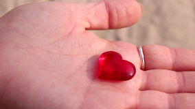 Woman shows red crystal heart in her hand Royalty Free Stock Photos