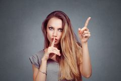 Woman shows shh, silence and attention listen to me signs royalty free stock photography