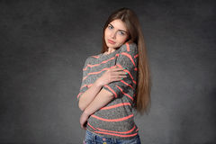 Woman shows softness against a dark background Royalty Free Stock Image