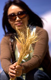 Woman shows stalks of wheat. Royalty Free Stock Image