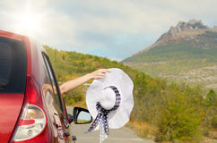 Woman shows sun hat from car Royalty Free Stock Images