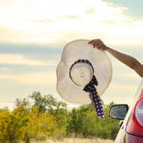 Woman shows sun hat from car Stock Photography