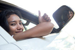 Woman shows thumb up from car. Young woman shows thumb up from open window of the white car stock photo