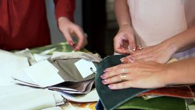 The woman shows to the customer textiles samples. On this video you can see as the woman shows to the client the materials and iskiza. The woman the businessman stock footage