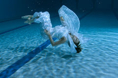 Woman shows an underwater show. Woman shows an underwater show, she is at the bottom of the pool Stock Photography