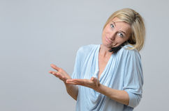 Woman shrugging her shoulders in ignorance. Attractive blond woman standing shrugging her shoulders in ignorance, indifference or confusion with a wry smile Royalty Free Stock Image