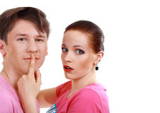 Woman shushing the man. Woman shuts man's mouth by index finger isolated on white background royalty free stock image