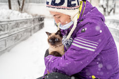 Woman with Siamese cat in winter Royalty Free Stock Images