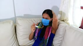 Woman with a sick face mask taking her temperature