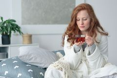 Woman on sick leave. Sitting in a bathrobe on bed and drinking warm tea with honey and lemon royalty free stock photo