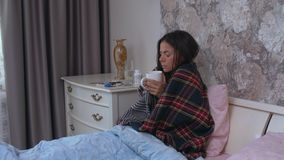 The girl sits on the bed is sick. A woman is sick and sits at home on the bed drinking from a mug stock video