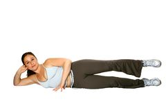 Woman on side doing leg raises. Active sports woman laying on her side, doing leg raises, isolated on white royalty free stock images