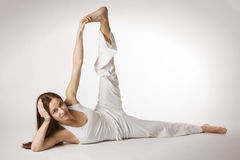 Woman side flank stretch Yoga posture (Parsvottana. Young lady practicing yoga side flank stretch (Parsvottanasana) in white clothes with red hair spread out on royalty free stock photos