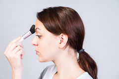 Woman in Side View Applying Makeup on Forehead Stock Photography