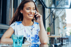 Woman at sidewalk cafe talking on the mobile phone Royalty Free Stock Image