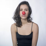 Woman sighing with red nose. A pretty young woman wearing red nose with an unhappy expression on face Stock Photos