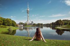 Woman sightseeing in Olympiapark, Munich. Brunette sitting on th. E green grass by lake looking on green park with tv tower, Bavaria, Germany Royalty Free Stock Photography