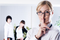 Woman with sign keep silence. Woman with a Keep it quiet expression in office Royalty Free Stock Image