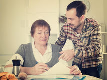Woman signing agreement. Aged women signing financial agreement with social worker at home Royalty Free Stock Images