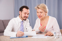 Woman signing agreement. Aged women signing financial agreement with social worker at home Royalty Free Stock Image