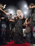 Woman Signing Autographs On Red Carpet. Young woman signing autographs on red carpet surrounded by paparazzi Royalty Free Stock Photos