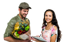Woman signing for bouquet delivery with smiling postman Royalty Free Stock Photo