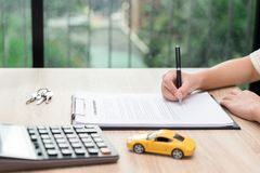 Woman signing car loan agreement contract with car key and calculator on wooden desk. Woman signing car loan agreement contract with car key and calculator on stock photography