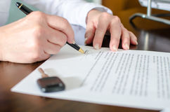 Woman signing a car purchase contract Stock Photography