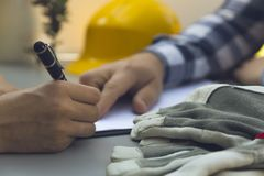 Woman signing construction contract with contractor. Yellow helm royalty free stock photos