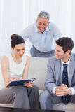 Woman signing a contract as husband and salesman are watching Stock Photo