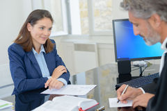 Woman signing contract with bank director Stock Images