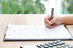 Woman signing contract with calculator on wooden desk. Woman signing contract with calculator on wooden desk Royalty Free Stock Image
