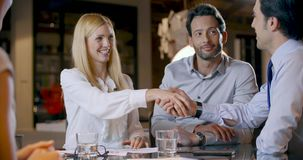Woman signing contract deal and handshake. Corporate business team work office meeting.Four caucasian businessman and stock video