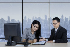 Woman signing a contract with her manager Stock Photography