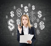 Woman signing contracts near dollar signs on blackboard Stock Photo